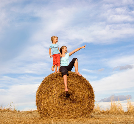 girl and boy standing on hay bale
