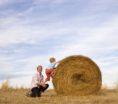 man helping boy to climb hay bale