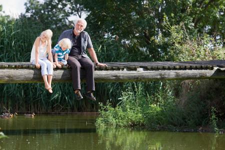grandfather and children on footbridge 免版税图像