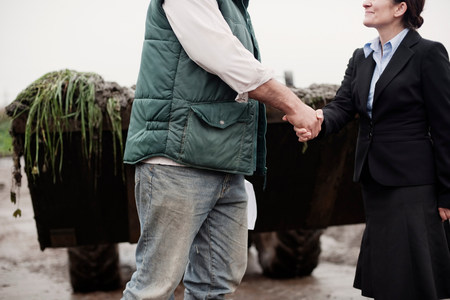 business woman shaking hands with farmer