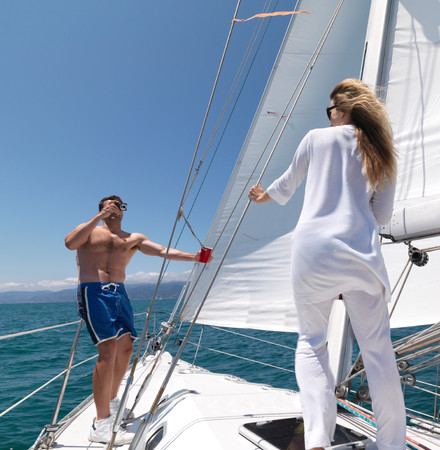 Man taking picture of woman on sailboat Stock Photo