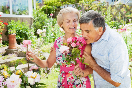man smelling flowers in woman\'s hand.