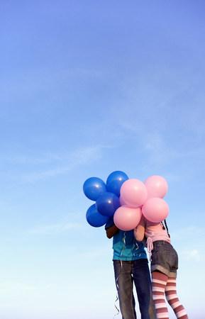 Two children hidden behind balloons