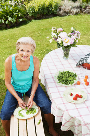 Mature woman peeling pods in garden. 免版税图像