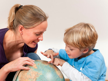 mother and son study globe