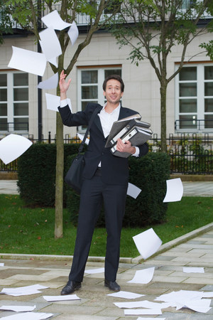 businessman surrounded by flying paper