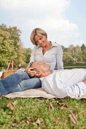 Middle aged couple on a picnic blanket Stock Photo