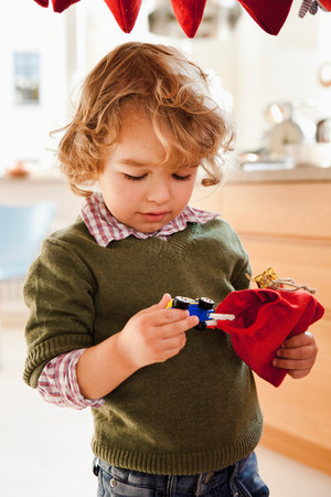 Young boy pulling toy out of gift sack Stock Photo