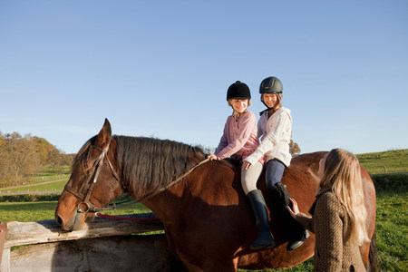 Woman talking with two girls on a horse