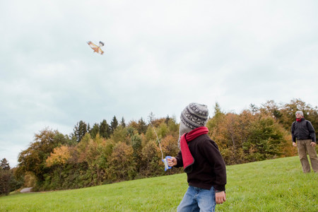 Father watching son flying a kite Imagens