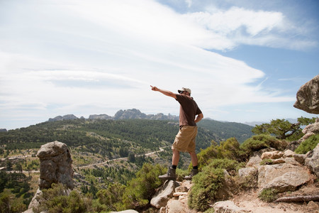 Man on a cliff pointing Stock Photo