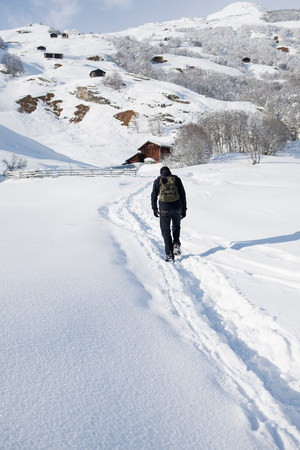 Man walking through snow in countryside