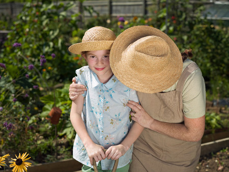 Young girl smiling with mother in garden Stock Photo