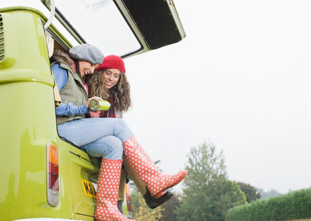 Women sharing hot drink Stok Fotoğraf