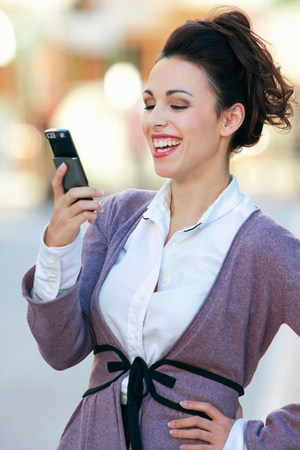 A woman laughing at a text message