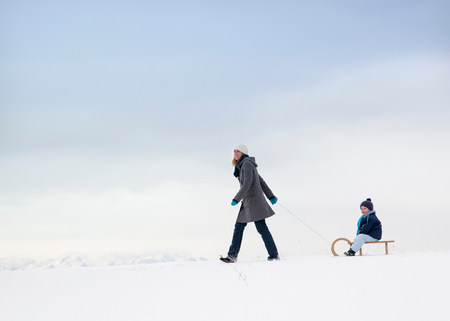 Mother pulling son on sled