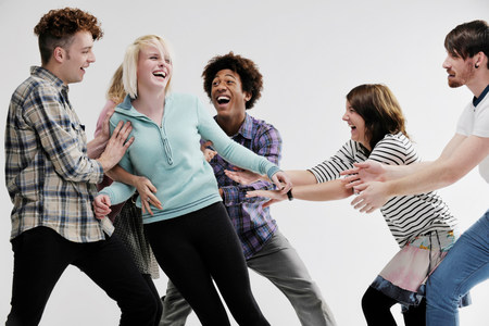 Group of young adults pushing each other