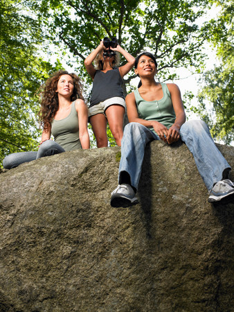 Women sitting on a rock in the woods Stock Photo