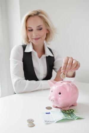 Woman dropping money into piggy bank Foto de archivo