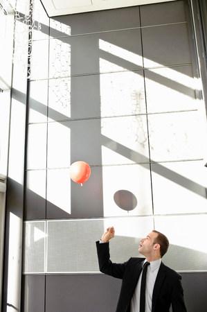 Man setting balloon free in office