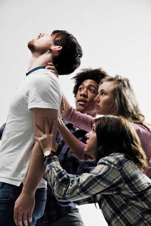 Male being supported by 3 people