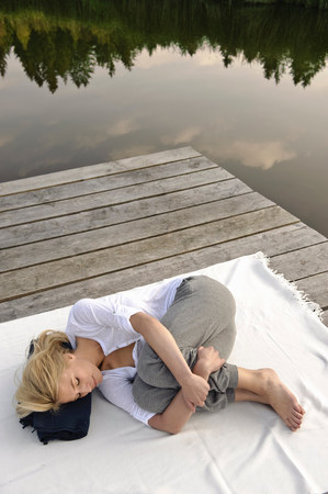 Young woman lying on blanket by lake Stock Photo