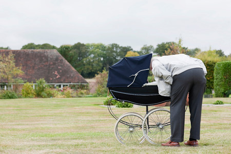 Grandfather looking at baby in pram