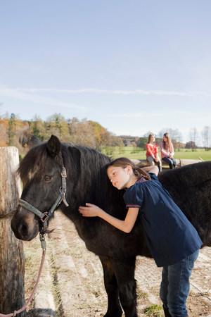 Girl stroking a pony Stock Photo
