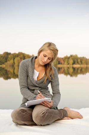 Young woman writing,sketching, by lake Stok Fotoğraf