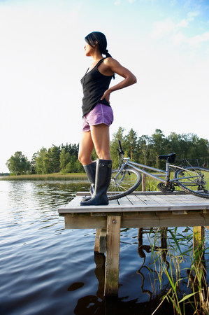 Woman with bike, at the end of a dock