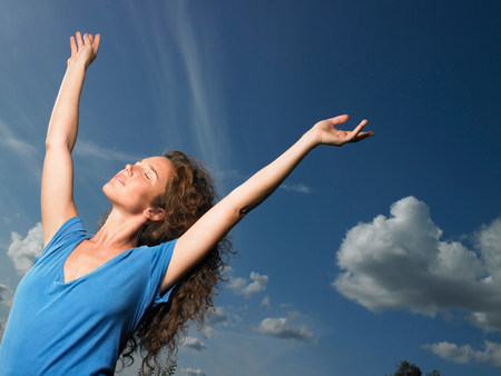 Woman spreading her arms towards the sky Imagens