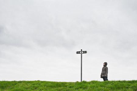Woman looking up at sign post