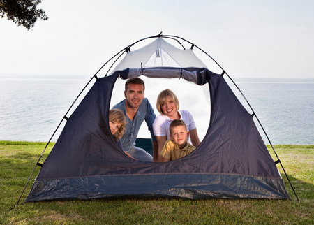 Family camping with tent by sea 免版税图像