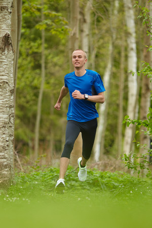 Man running in forest Imagens