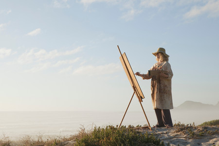Mature woman painting in landscape