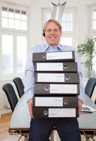 Businessman carrying pile of files Reklamní fotografie