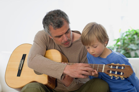 Man showing son guitar Фото со стока
