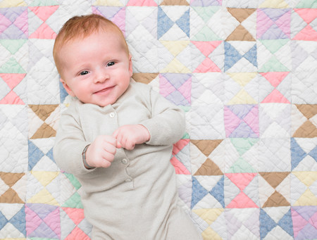 Smiling baby on quilt