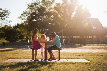 3 girls sitting in park painting Imagens