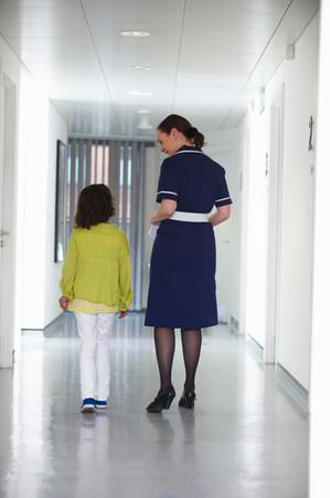Nurse and young girl walking in corridor