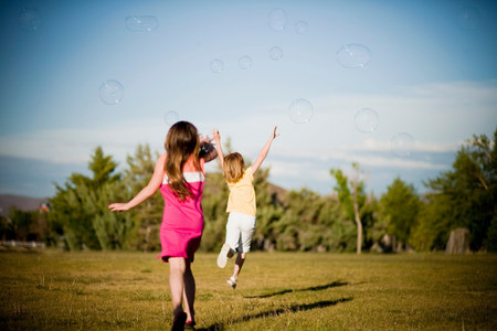 2 young girls chasing bubbles in park Banque d'images