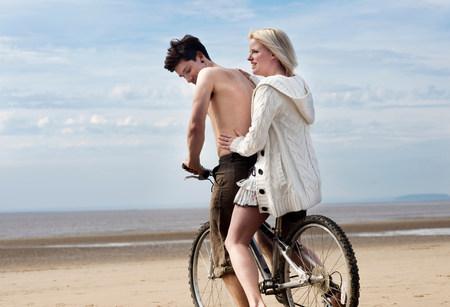 Couple on bike on beach