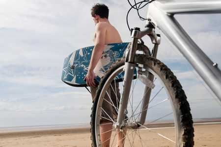 Man on beach with bike and boogie board