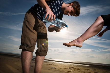 Man washing womans feet on beach