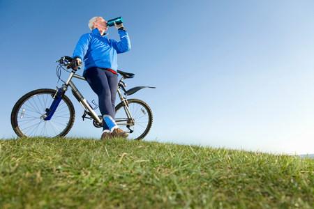 Senior man drinking water on bike ride Imagens