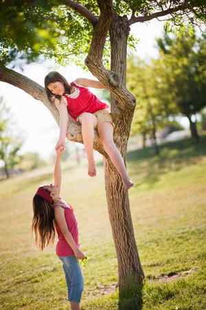 Girl helping friend climb tree