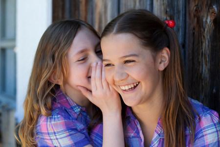 Girl whispering in her friends ear Standard-Bild