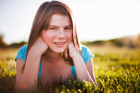 Young girl in grass smiling Stockfoto