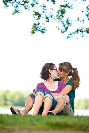 Two women kissing in park Stok Fotoğraf
