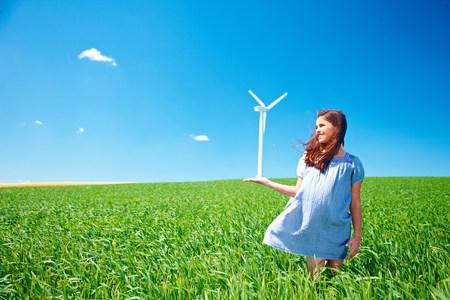 Girl on field with wind turbine